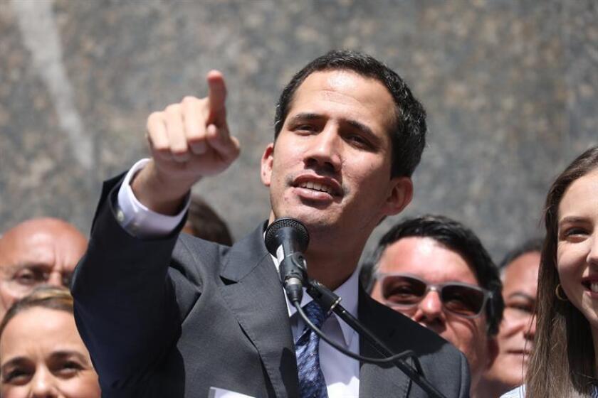 El líder del Parlamento y autoproclamado presidente encargado de Venezuela, Juan Guaidó (C), habla este viernes durante su primera aparición pública desde que se adjudicó las competencias del Ejecutivo ante miles de personas, en una plaza en el este de Caracas (Venezuela). EFE