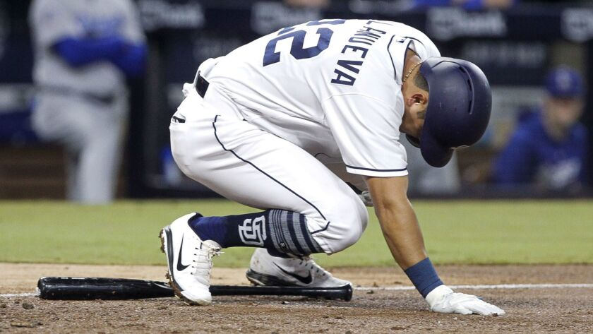 The Padres' Christian Villanueva drops to the ground after being hit by a pitch from Dodgers' pitcher Kenta Maeda in the fifth inning at Petco Park in San Diego on Wednesday.
