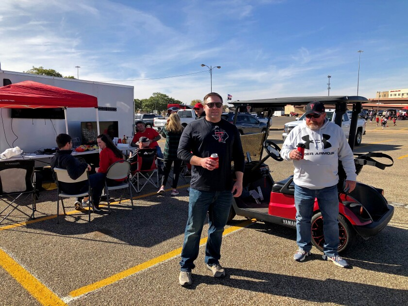 Two men hold cans of beer as people tailgate in a parking lot