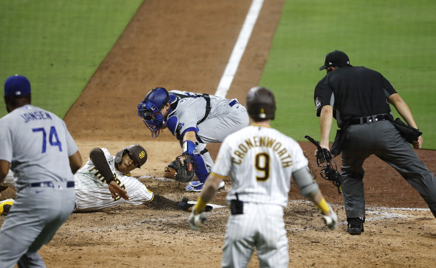 San Diego Padres Trent Grisham is tagged out at home plate by Los Angeles Dodgers catcher Will Smith as he tries to score tagging up in the 9th inning at Petco Park on August 5, 2020.