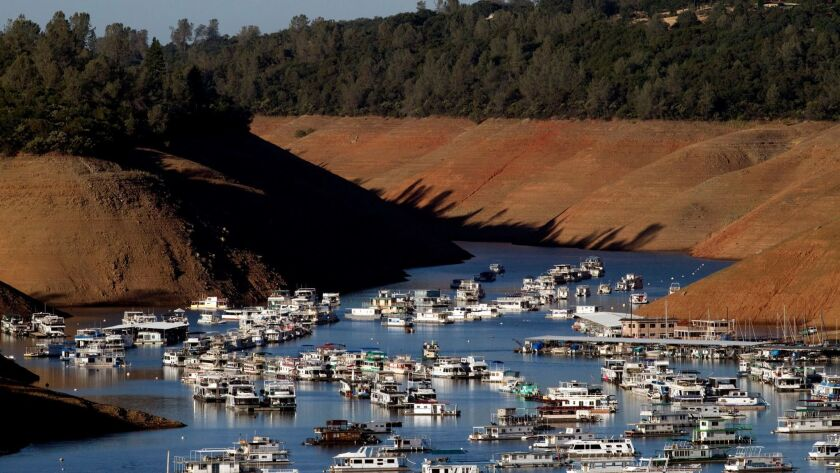 Severe drought conditions are evident as hundreds of houseboats are dwarfed by steep banks showing the water level down 160 feet from the high-water mark at Bidwell Canyon Marina on Lake Oroville on June 21, 2014.
