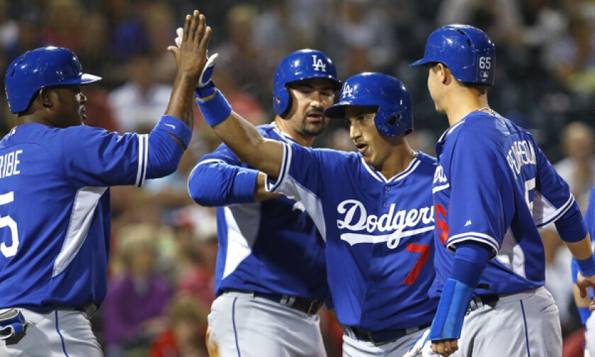 Dodgers infielder Alex Guerrero, second right, is congratulated by teammates Juan Uribe, left, and Adrian Gonzalez, second left, after hitting a fifth-inning grand slam in a Cactus League game against the Cincinnati Reds on Wednesday.