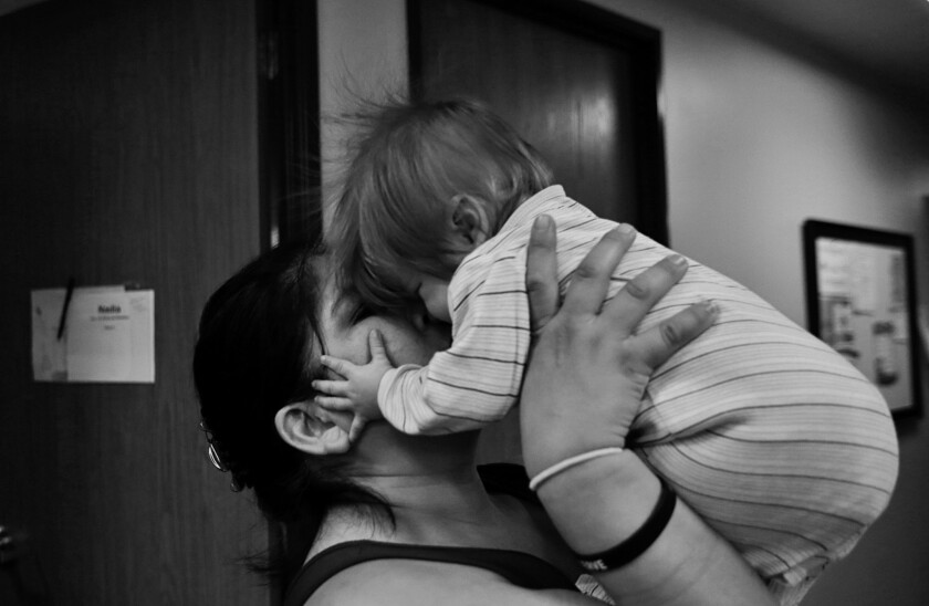 Nadia, 37, kisses her son Sebastian. She and her children became homeless after she left an abusive marriage.