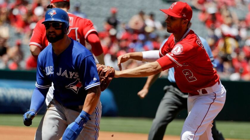 Los Angeles Angels shortstop Andrelton Simmons, right, tags Toronto Blue Jays' Kevin Pillar in a run