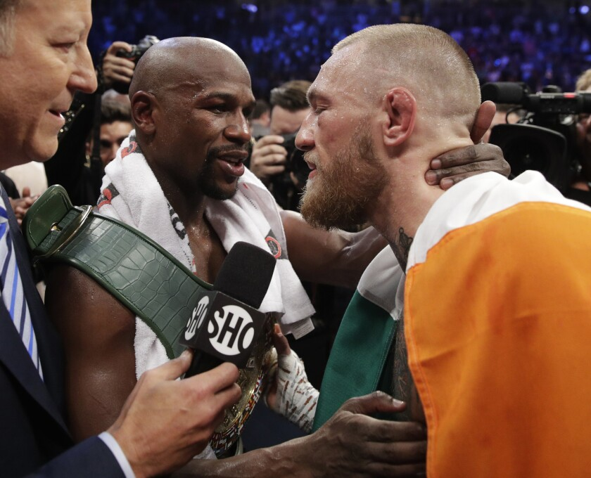 Floyd Mayweather Jr. embraces Conor McGregor after their super-welterweight fight.