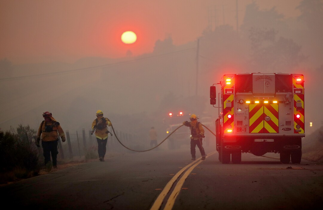 Firefighters carry hose