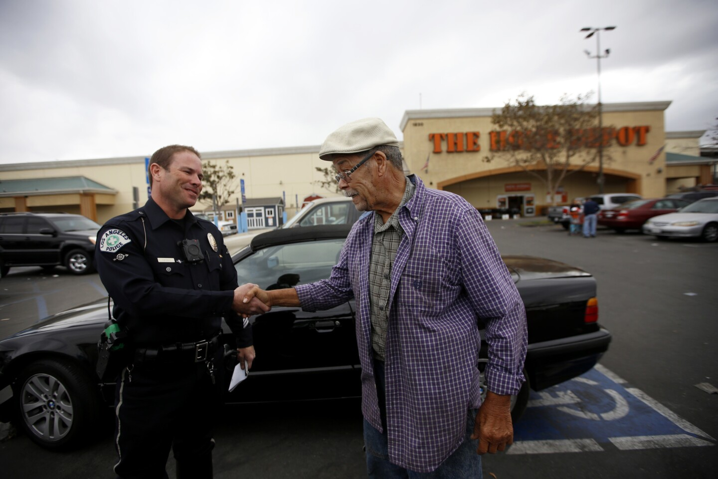 L.A. police Officer Ben Yasnyi, left, greets E. Lagemann, 80, after checking the motorist's disabled placard in a parking lot in South Los Angeles.