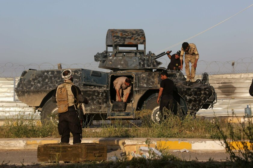 Members of Iraqi Shiite militant group called Imam Ali Brigades prepare their armoured vehicle at the front line with Islamic State group in Tikrit, 130 kilometers (80 miles) north of Baghdad, Iraq, Saturday, March 14, 2015. Iraqi military officials have said they expect to reach the center of Tikr