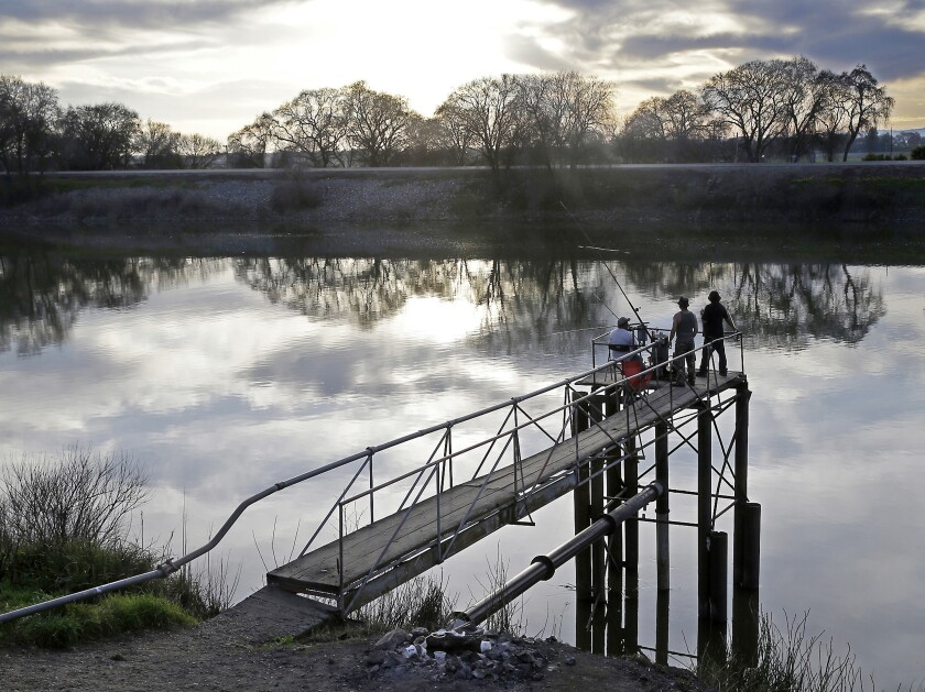 FILE - In this Feb. 23, 2016 file photo, people fish along the Sacramento River in the San Joaquin-Sacramento River Delta, near Courtland, Calif. Gov Gavin Newsom proposed new rules on Tuesday, Feb. 4, 2020, to keep more water in the delta while restoring 60,000 acres of habitat for endangered species and generating more than $5 billion in new funding for environmental improvements. The framework, if approved, would be in place for 15 years. (AP Photo/Rich Pedroncelli, File)