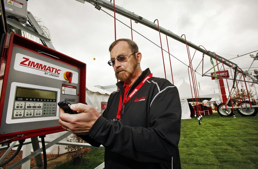 Dirk Lenie, vice president of global marketing for Lindsay International, demonstrates wireless irrigation management software aimed at helping farmers use less water at the 2014 World Ag Expo in Tulare, Calif.