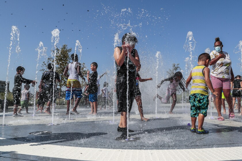 Children frolic in a playground water fountain on Labor Day.