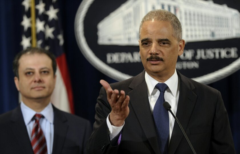 Attorney General Eric Holder, right, accompanied by U.S. Attorney for the Second District Preet Bharara, announces a $1.2 billion settlement with Toyota over its disclosure of safety problems, Wednesday, March 19, 2014, during a news conference at the Justice Department in Washington. (AP Photo/Susan Walsh)