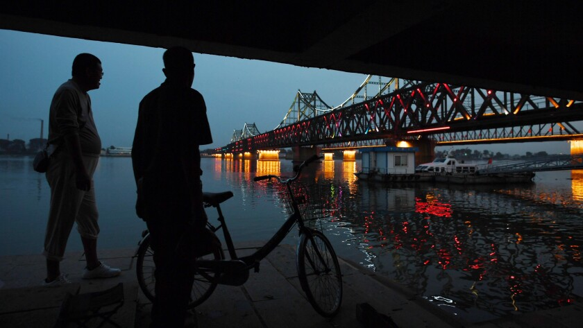 Two Chinese men chat near the China-North Korea Friendship Bridge between the North Korean town of Sinuiju (rear) and Dandong (foreground), in northeast China on Sunday.