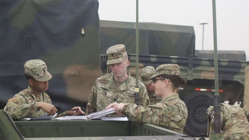 Army Staff Sgt Cathrine Schmid (far right) oversees several soldiers in March as they conduct vehic