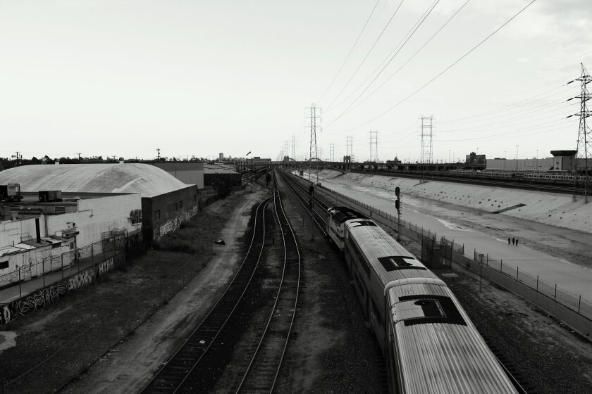 Train tracks parallel the Los Angeles River.