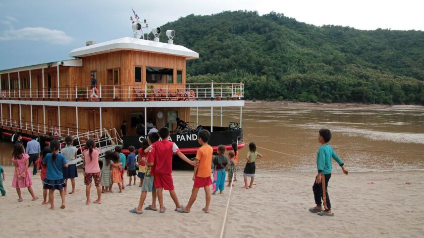A typical greeting party meets our boat, the Champa Pandaw, on a village stop in Laos. CREDIT: Norm