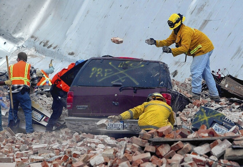 Rescue workers uncover cars, some with people trapped inside, along Park Street in Paso Robles after a magnitude 6.5 earthquake struck the city on Dec. 22, 2003.