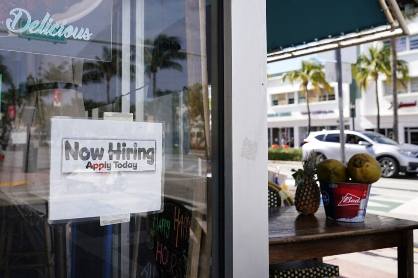 "A ""Now Hiring,"" sign is shown in the window of a restaurant"