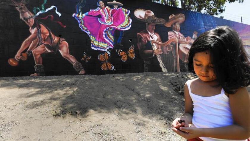 """El jueves, Long Beach dedicó el parque conmemorativo Jenni Rivera Memorial Park en honor a la cantante mexicano estadounidense quien murió en un accidente aéreo en el 2012. La nieta de Rivera, Jaylah Hope Yanez, juega con una mariposa cerca del mural del parque, apodado la """"Mariposa del barrio""""."""
