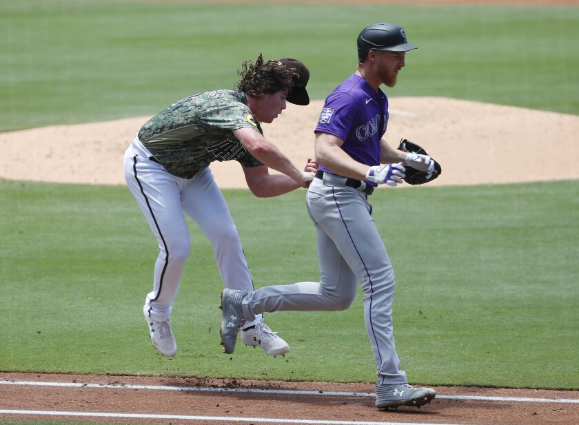 Padres pitcher Ryan Weathers gets tripped up as he tries to tag out the Rockies' Jon Gray