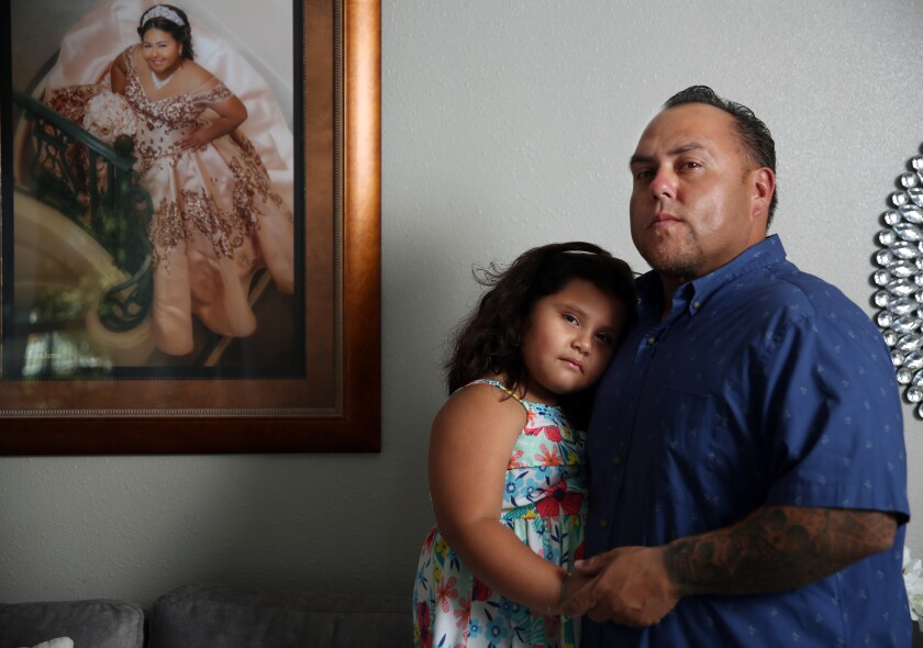 Rafael Saavedra and his daughter Gianna, 5. A framed picture of his oldest daughter, Gizzelle, hangs beside them.