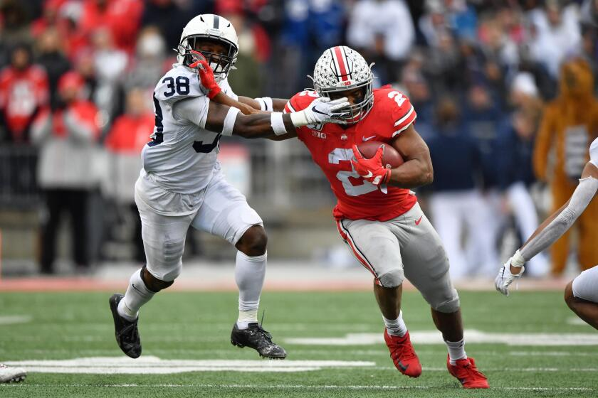 Ohio State running back J.K. Dobbins fends off Penn State safety Lamont Wade on Nov. 23, 2019.
