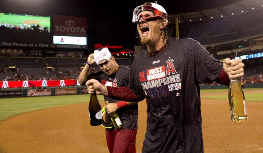 Angels pitcher Jered Weaver, right, and center fielder Mike Trout celebrate after the team won the AL West title on Wednesday night in Anaheim.