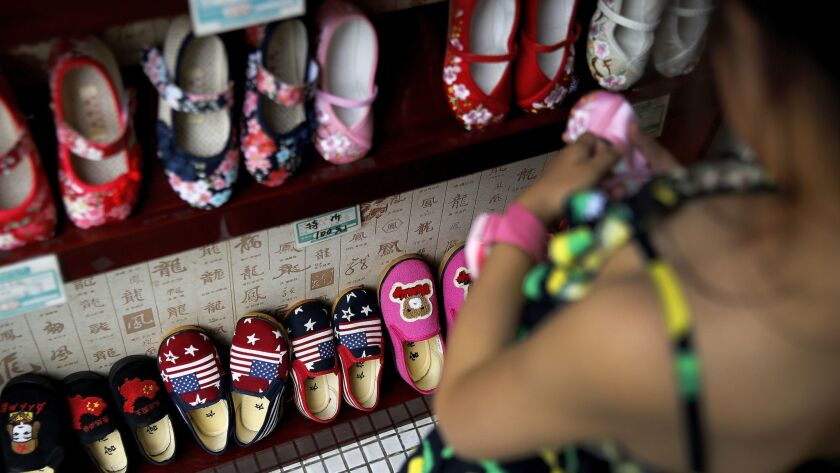 In this July 13, 2018, photo, a child selects shoes as Chinese made children shoes carrying a Chines
