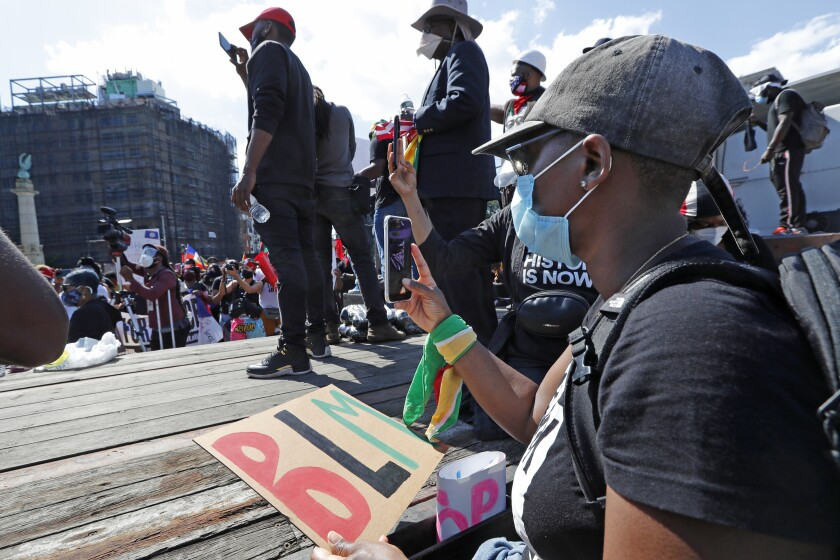 People record speakers and the crowd during a Caribbean-led Black Lives Matter rally at Brooklyn's Grand Army Plaza, Sunday, June 14, 2020, in New York. (AP Photo/Kathy Willens)
