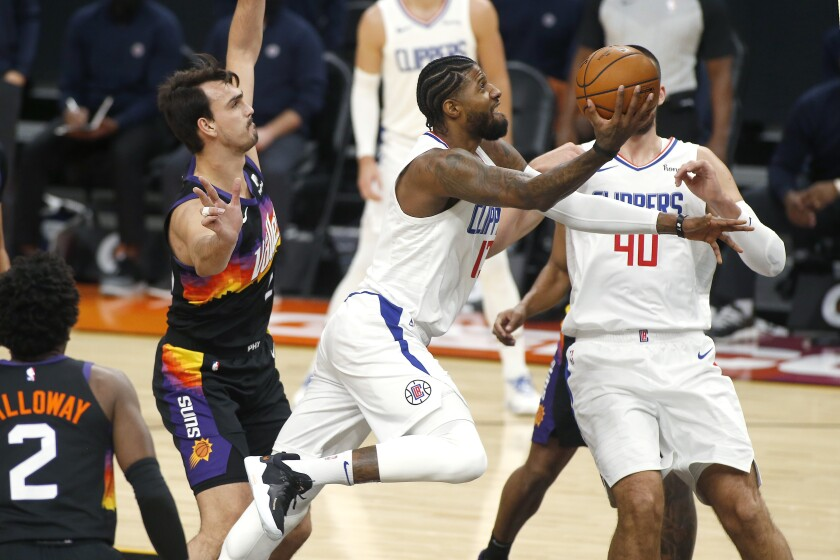 Clippers forward Paul George drives to the basket against the Suns on Jan. 3, 2021, in Phoenix.