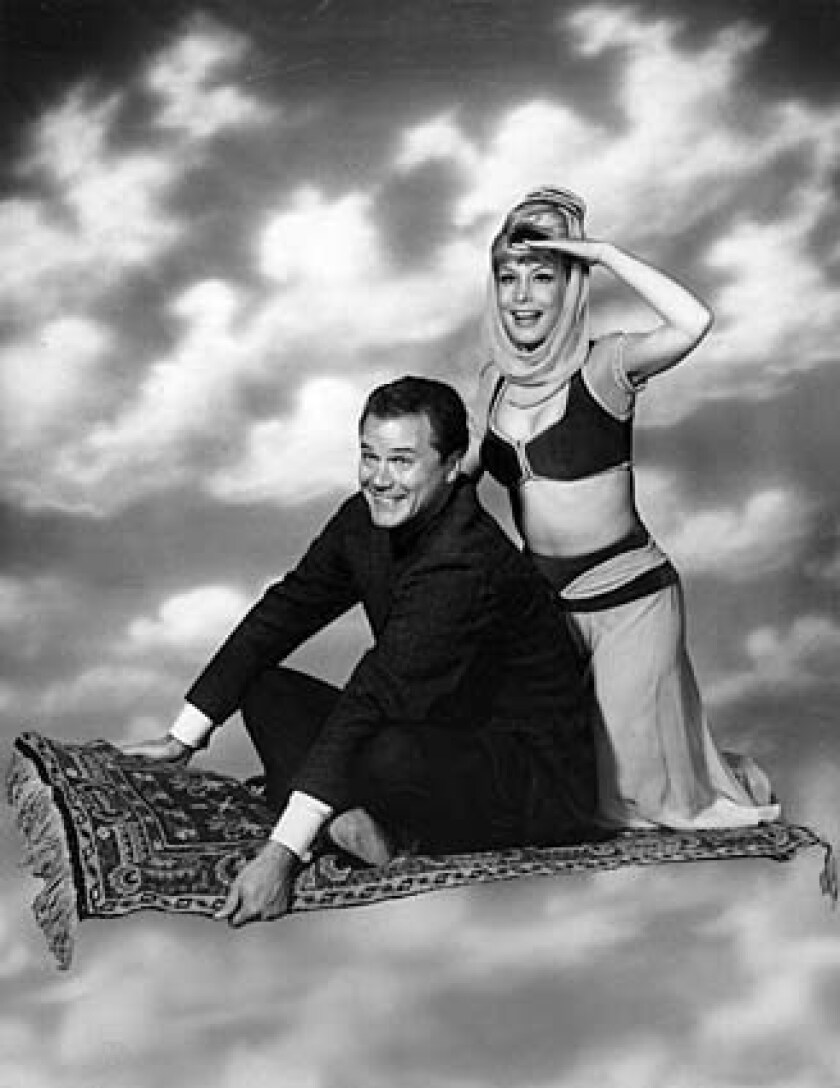 """""""I Dream of Jeannie"""" cast members Larry Hagman and Barbara Eden in a 1965 publicity photo."""