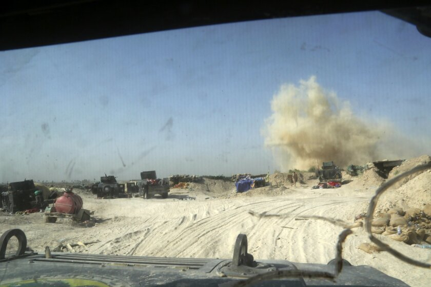In this photo picture taken through the windshield of an Iraqi army armored vehicle, smoke rises near Iraqi counterterrorism forces after Islamic State militants launch a mortar shell, in the Nuaimiya neighborhood of Fallujah, Iraq, Wednesday, June 1, 2016. The U.N. children's fund has issued a sta