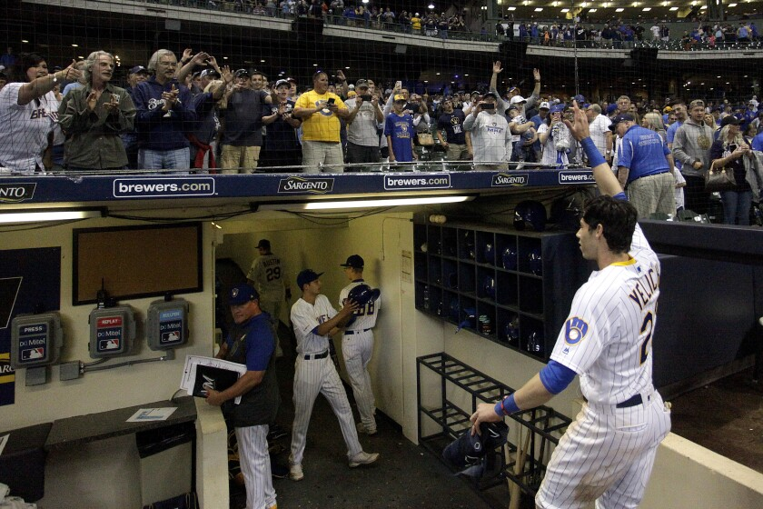 FILE - In this Sept. 7, 2019, file photo, fans cheer as Milwaukee Brewers' Christian Yelich walks off the field after driving in the winning run with a double during the ninth inning of the team's baseball game against the Chicago Cubs in Milwaukee. Major League Baseball players and owners are currently caught in a bitter dispute over how to start amid the coronavirus pandemic. Both sides occasionally mention fans, talking about doing right by them. (AP Photo/Aaron Gash, File)