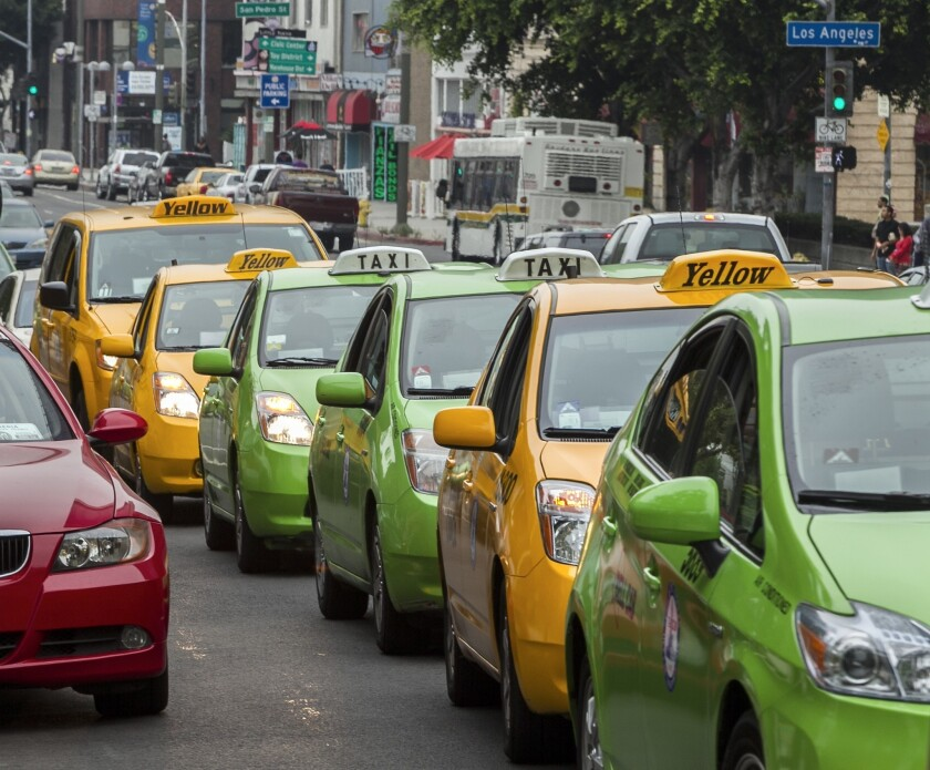 Taxi drivers circle Los Angeles City Hall in their cabs to protest unregulated ride-share services - such as Uber, Lyft and Sidecar - being promoted through smart-phone applications and social media.