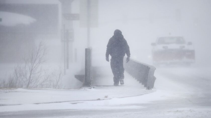 A man crosses Crow Creek during a blizzard on Wednesday, March 13, 2019, in Cheyenne, Wyo. Heavy sn