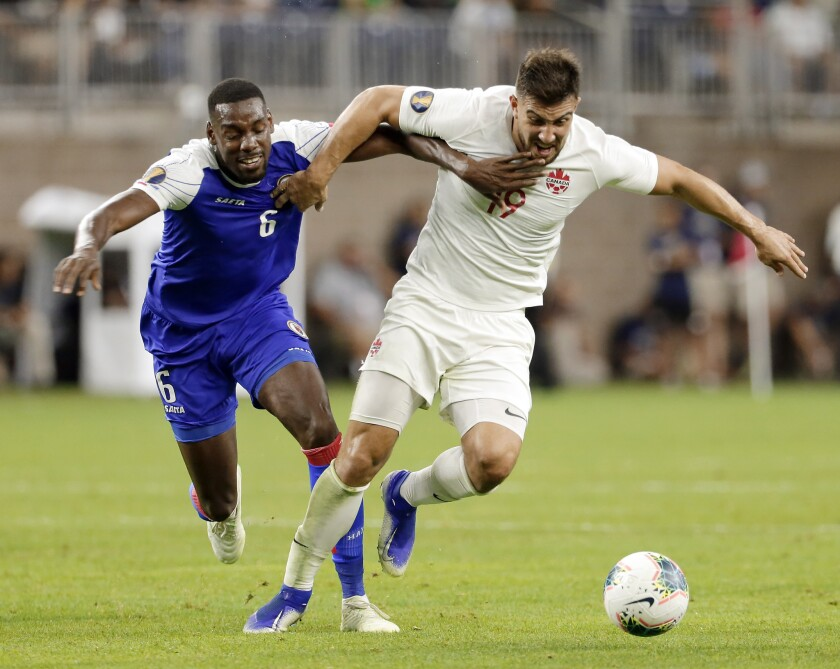Haiti defender Jems Geffrard (6) and Canada forward Lucas Cavallini (19) pull on each other as they