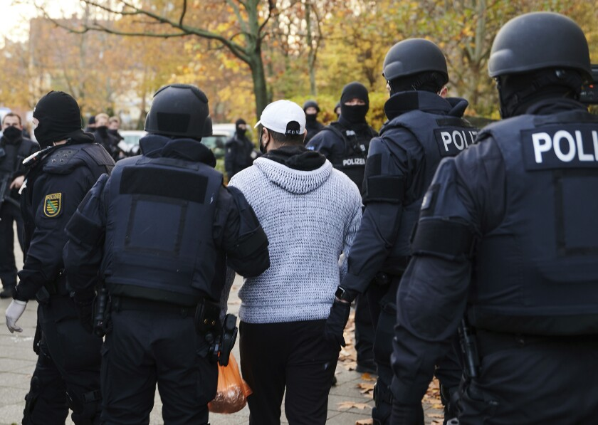 Police officers escort a person for an identity check in Berlin, Germany, Tuesday, Nov. 17, 2020. Almost a year after the art theft in Dresden's Green Vault, police arrested three suspects on Tuesday morning in Berlin. Since the early morning, a total of 18 objects have been searched. (Annette Riedl/dpa via AP)