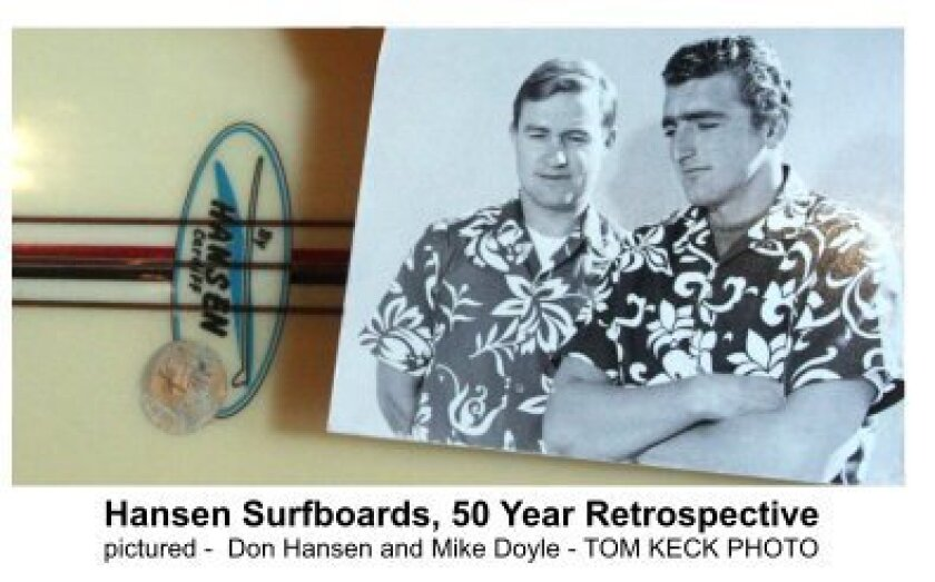 Central to the display are vintage Hansen Surfboards, advertisements, photos and more. In this Tom Keck photo, Don Hansen (left) and Mike Doyle sport the Hawaiian shirts.