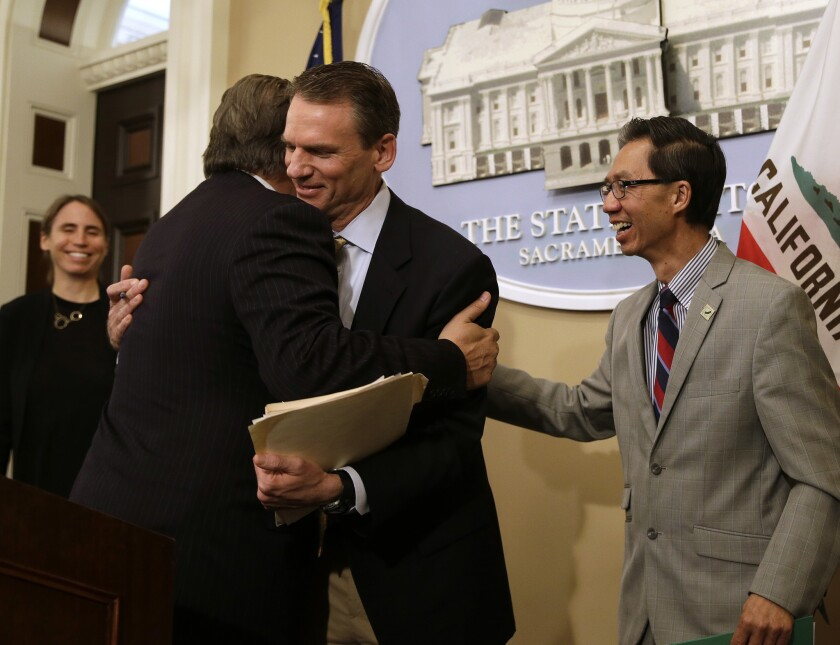 State Sen. Bob Hertzberg (D-Van Nuys), left, and Assemblyman Ed Chau (D-Arcadia), right, celebrate with Alastair Mactaggart, center, whose efforts led to the legislation, after the Legislature approved their data privacy bill in 2018.