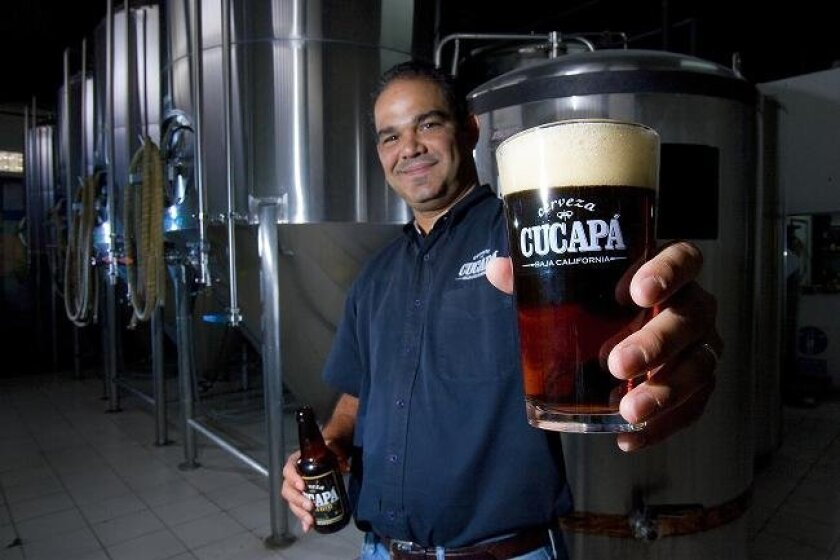 In Mexicali, CEO Mario Garcia of Cucapa Brewery holds up one of his company's more popular ales.