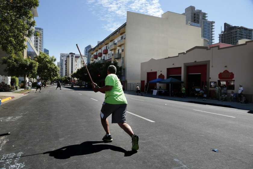 """""""Stickball Willie"""" Blas takes a swing for the Young Stars team during the 15th Annual San Diego Labor Day Stickball Tournament in Little Italy. The tournament uses Bronx-style rules."""