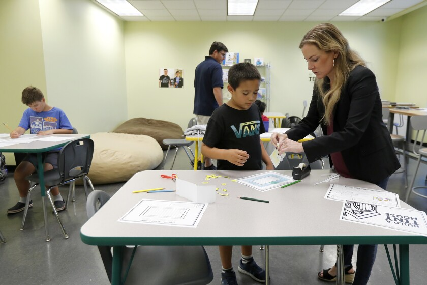 Principal Lisa Reid, right, works with a fourth-grader in the Innovation Lab at the STEM3 Academy in Irvine. It's the only K-12 school in the nation to provide STEM curriculum to students with social and learning differences.
