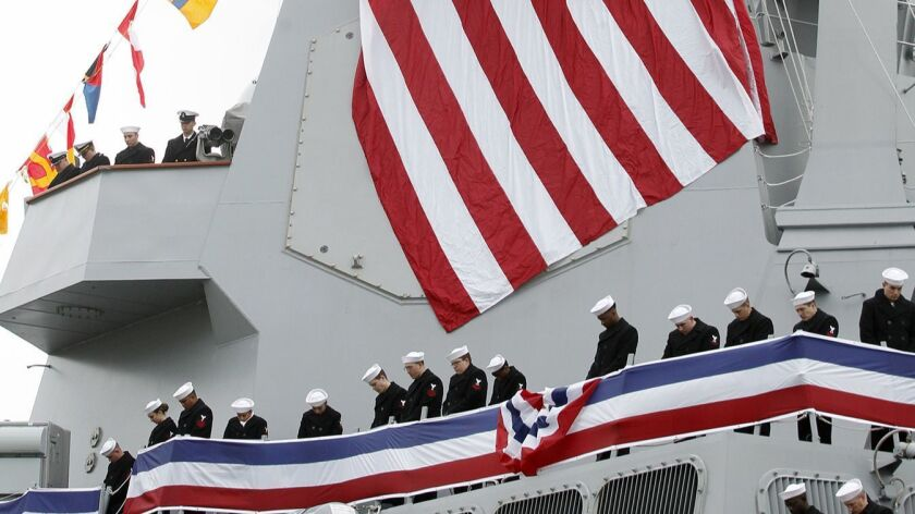 Crew members line the rails of the USS Thomas Hudner and bow their heads in prayer during an invocat
