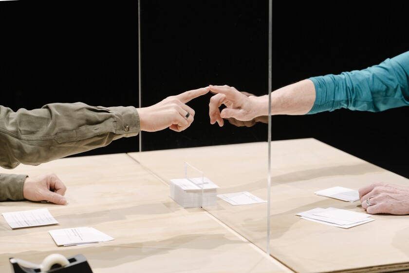 "People touch fingers to the plexiglass separating them as part of ""An Encounter."""