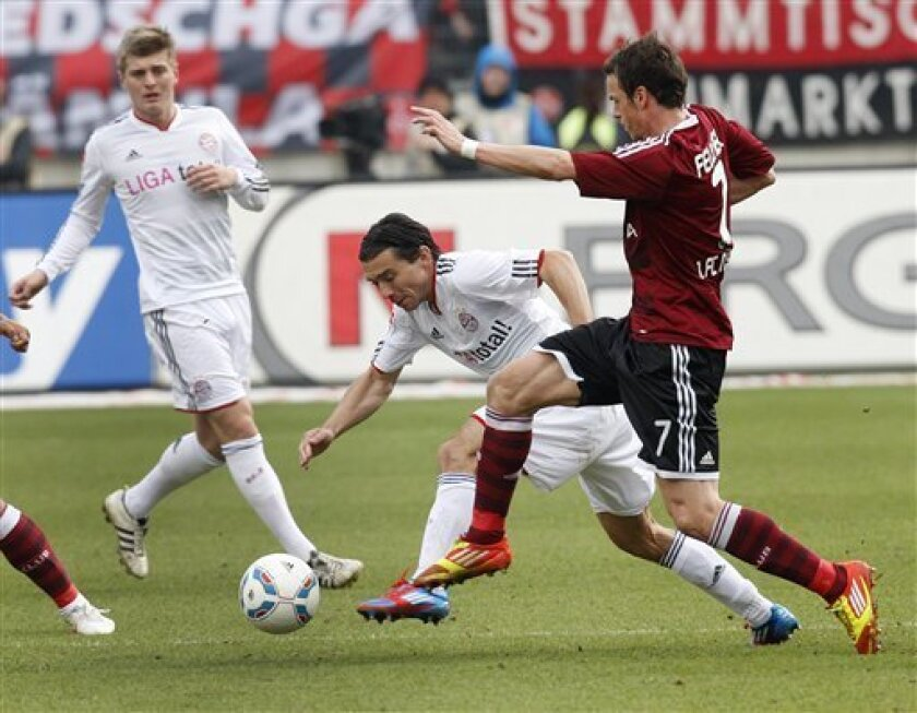 Nuremberg's Marus Feulner, right, and Munich's Danijel Pranjic, center, challenge for the ball during the German first division Bundesliga soccer match between 1.FC Nuremberg and Bayern Munich in Nuremberg, Germany, Saturday, March 31, 2012. (AP Photo/Michael Probst) NO MOBILE USE UNTIL 2 HOURS AFT