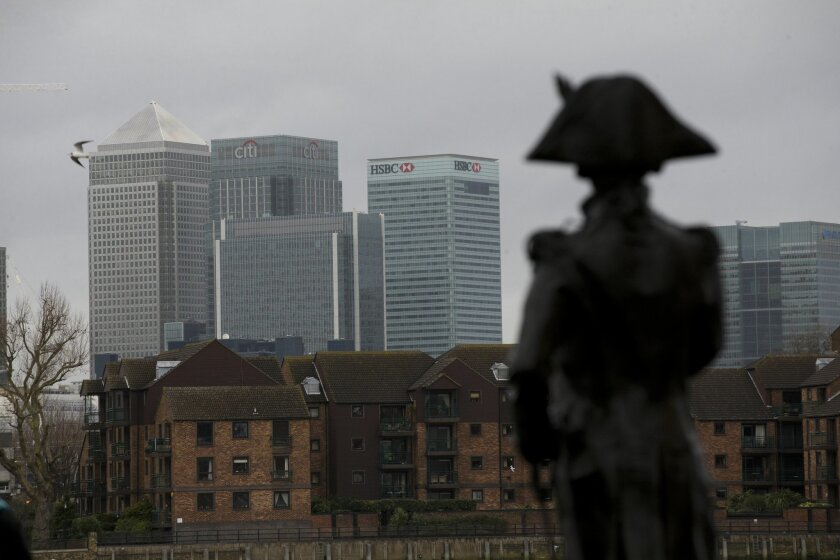 In this Monday Feb. 8, 2016 photo, the HSBC headquarters building stands amongst other skyscrapers in the Canary Wharf business district of London, with a statue of Lord Nelson in the foreground. International bank HSBC said Sunday Feb. 14, it has decided to keep its headquarters in London after co