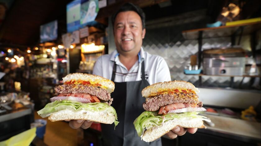MANHATTAN BEACH, CA -- JUNE 21, 2019: Martin Anguiano, manager for 26 years, serves up huge burgers