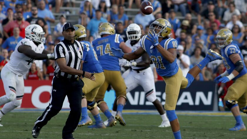 PASADENA, CALIF. - SEP. 1, 2018. UCLA tight end Caleb Wilson bobbles the ball before making a cat
