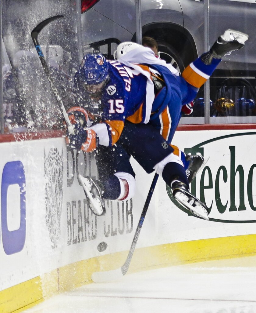 New York Islanders' Cal Clutterbuck (15) checks Washington Capitals' Dmitry Orlov (9) during the second period of an NHL hockey game Thursday, Feb. 18, 2016, in New York. (AP Photo/Frank Franklin II)