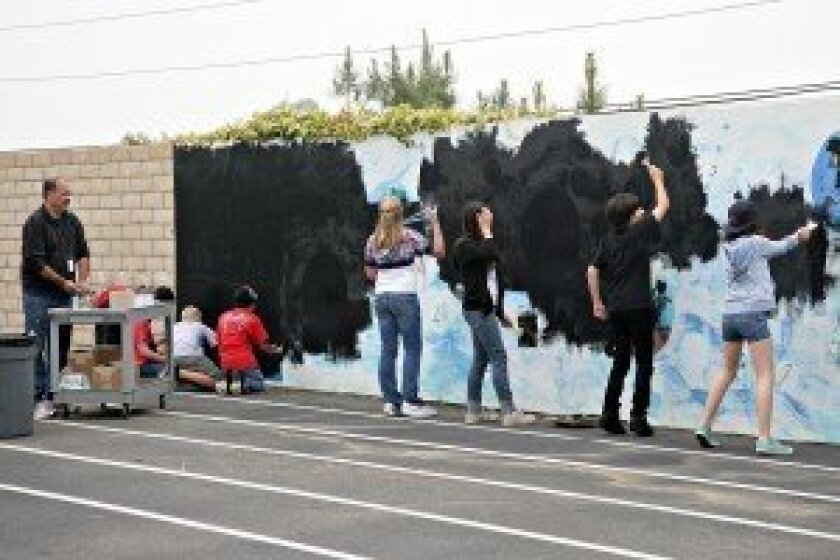 Students paint alongside Salas in the developing mural.